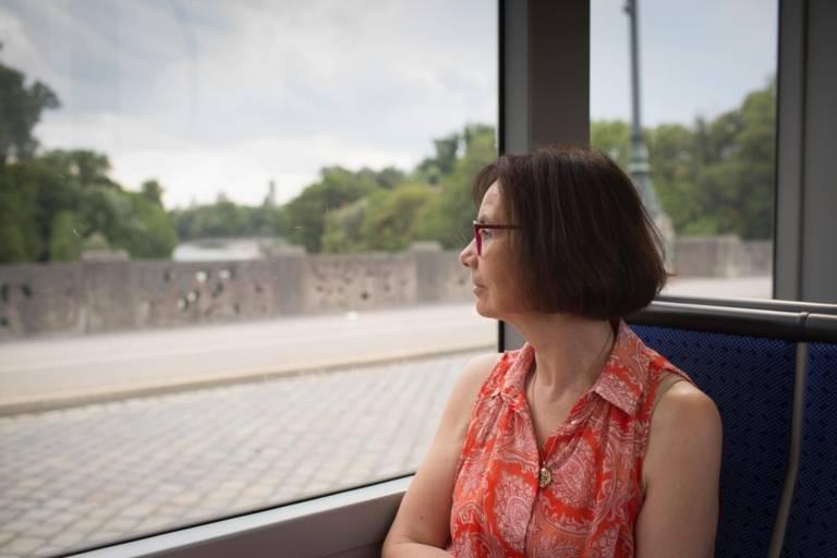Frau schaut aus einer Trambahn auf die Maximilansstraße in München.