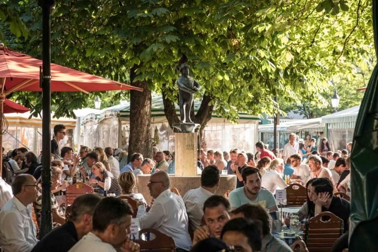 Menschen im Biergarten auf dem Viktualienmarkt in München.