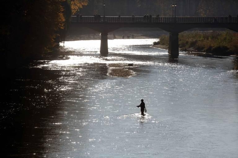 Ein Angler steht in der Isar in München und angelt.