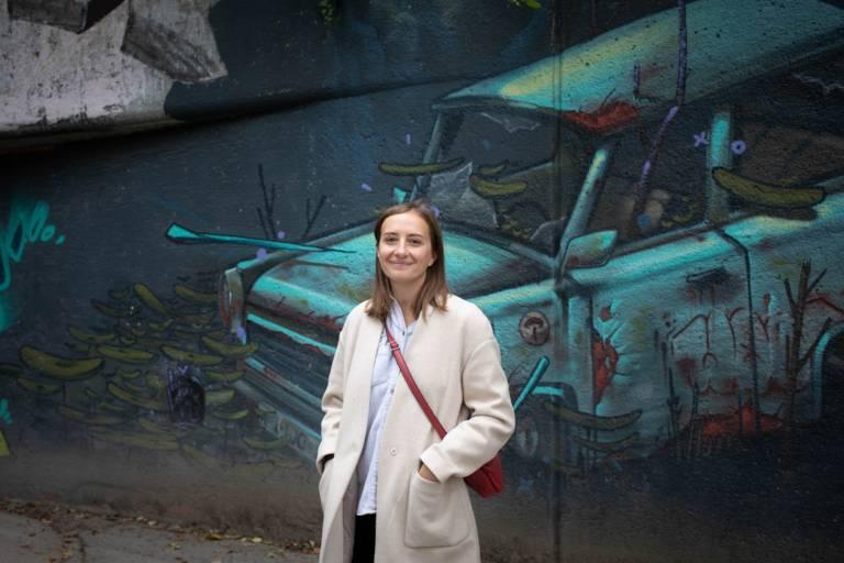 Junge Frau steht vor einem Mural in München.