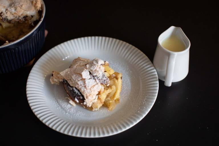 Eine Süßspeise mit Puderzucker auf einem Teller neben einem Kännchen mit Vanillesoße