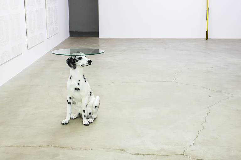 Ein Dalmatiner aus Porzellan dient als Beistelltischchen mit einer runden Glasplatte auf dem Kopf.