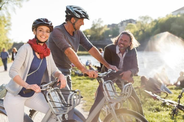 Drei Fahrradfahrer stehen an der Isar in München und unterhalten sich.