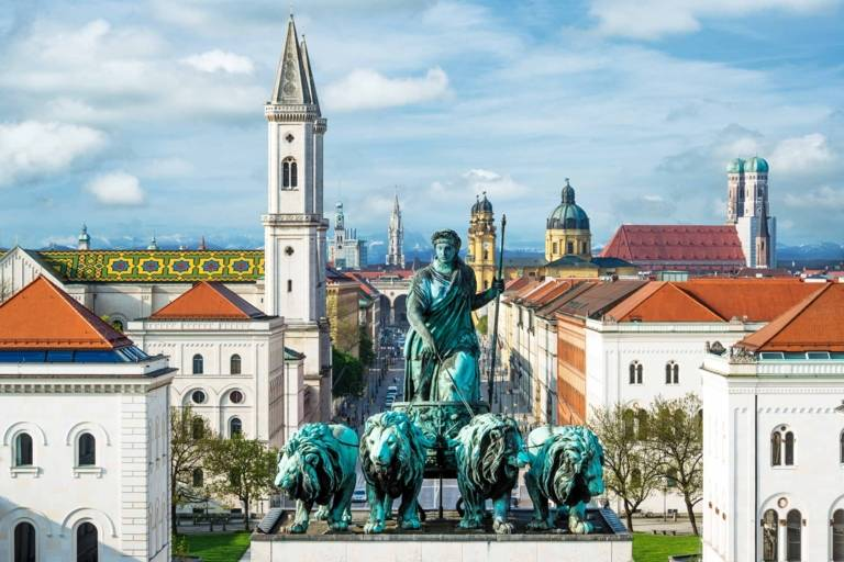Lion-quadriga on top of the Siegestor in Munich with the skyline of the inner city of Munich and the alps in the background.