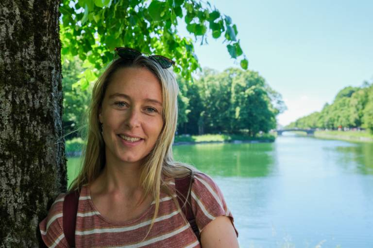Sarah Althaus steht am Nymphenburger Schlosskanal an einem Baum.