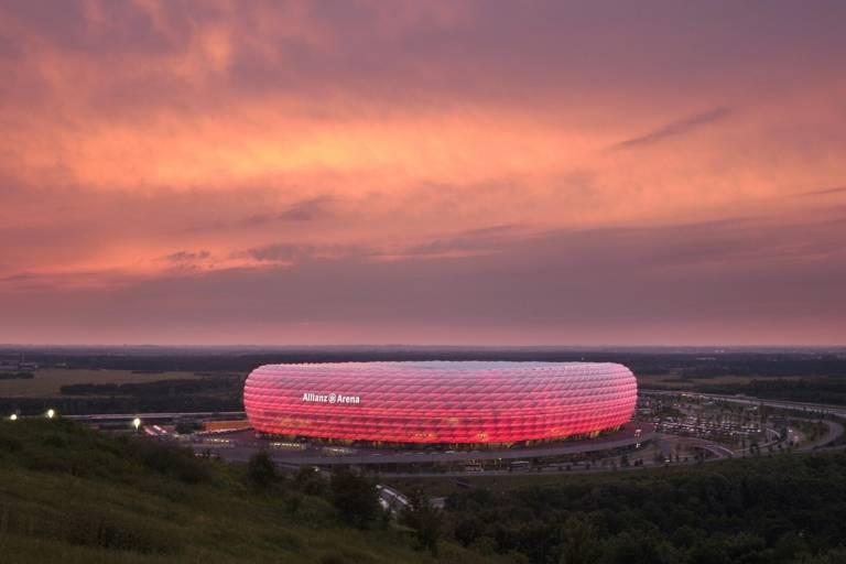 Die Allianz-Arena in München leuchtet rot im Abendlicht.