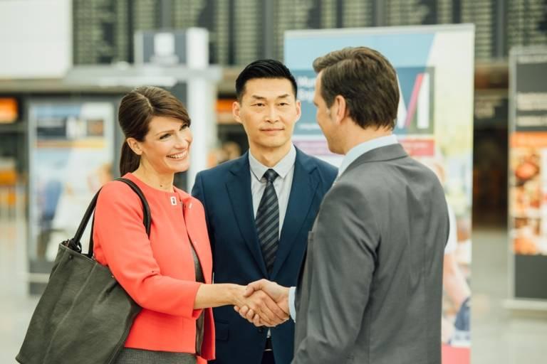 Eine Frau und ein Mann begrüßen sich am Flughafen in München.