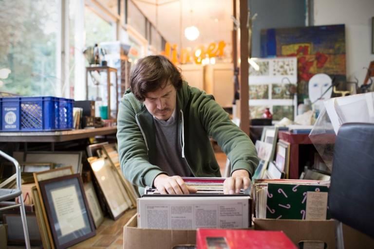 Ein Mann kramt in einem Antiquitätenladen in München in einem alten Schallplatten-Karton.