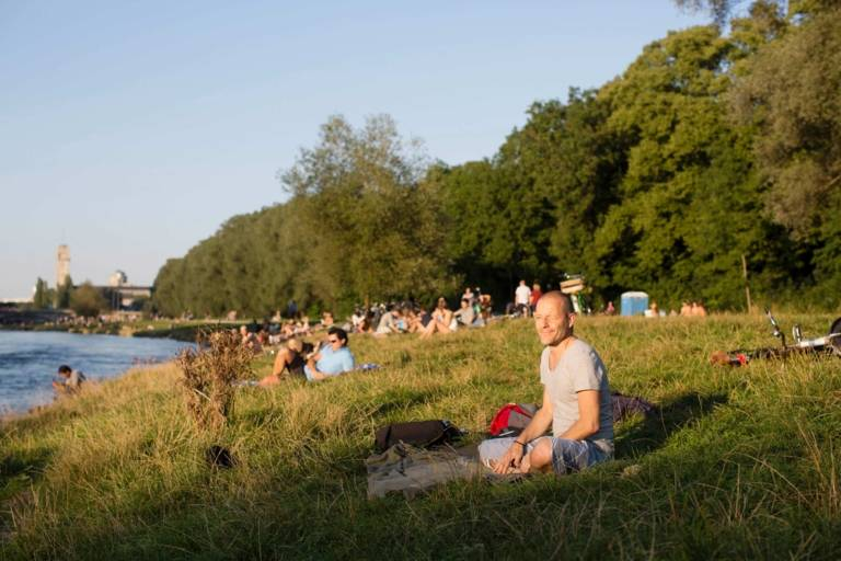 Menschen sitzen am Ufer der Isar.