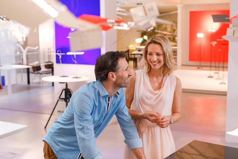 Eine Frau und ein Mann unterhalten sich in der Ingo Maurer Lichtdesign Ausstellung in München.