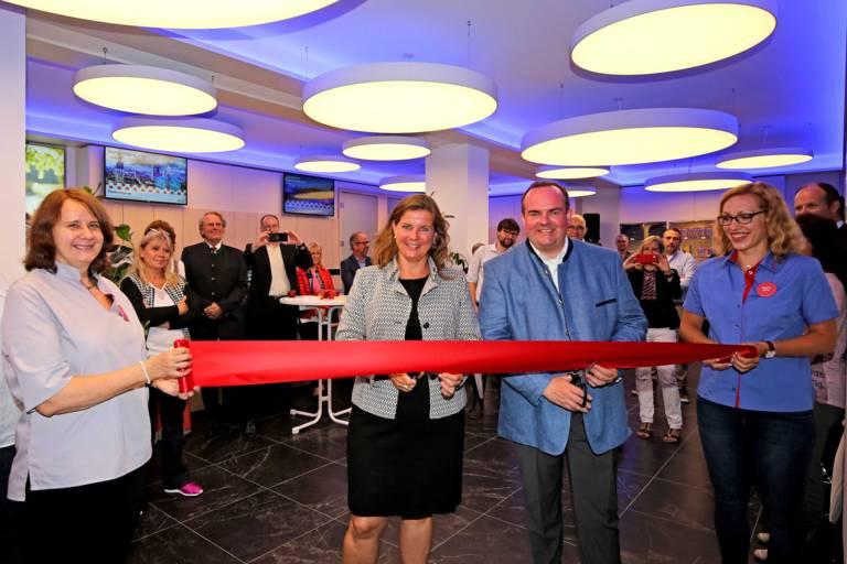 Geraldine Knudson, die Leiterin von München Tourismus und Wirtschaftsreferent Clemens Baumgärtner durchschneiden ein rotes Band in der Tourist-Information am Hauptbahnhof.