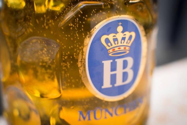 Sprudelndes Bier in einem Glaskrug mit dem Logo der Münchner Hofbräu Brauerei