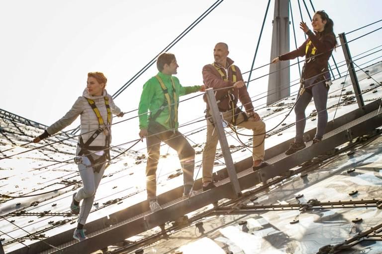 Vier Personen stehen auf dem Dach des Olympiastadions in München.