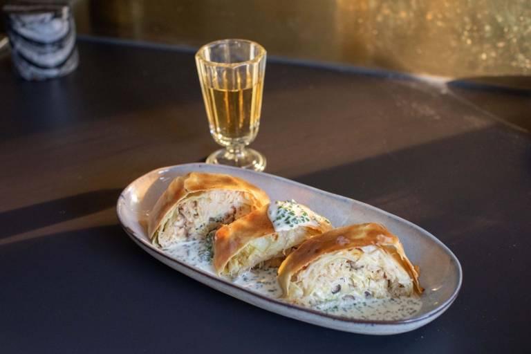 Krautrahmstrudel auf einem Teller steht neben einem Glas Wein
