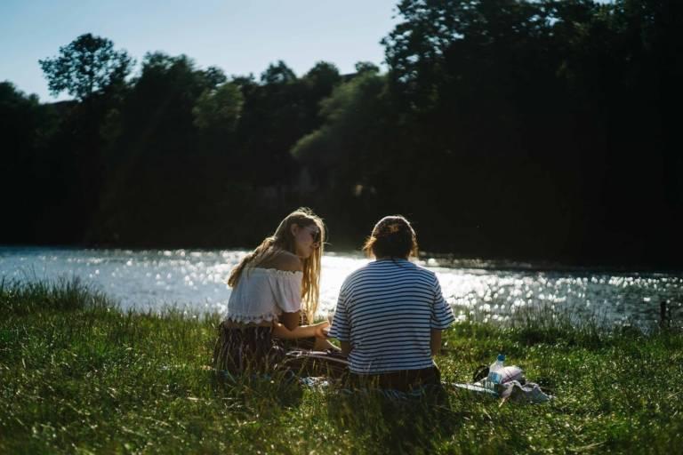 Zwei Frauen am Isarufer im sommerlichen München