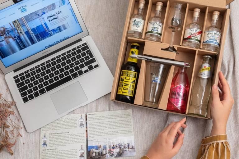 Ein Laptop, eine Gin Broschüre und ein mehrere Flaschen Gin in einem Testkit stehen auf einem Tisch.