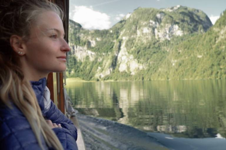A young woman watching the Königssee from the ship