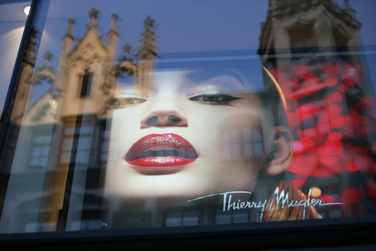 Eine Kirchen-Silhouette spiegelt sich im Schaufenster eines Geschäftes in München.