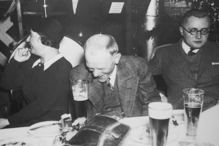 Karlstadt und Valentin trinken Bier und lachen.