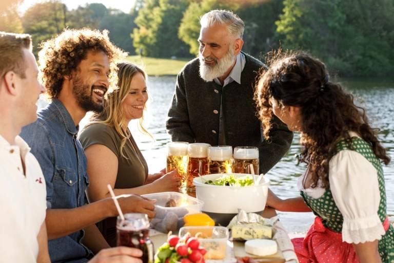 Ein Mann bringt mehrere Mass Bier an einen Tisch in einem Biergarten in München.
