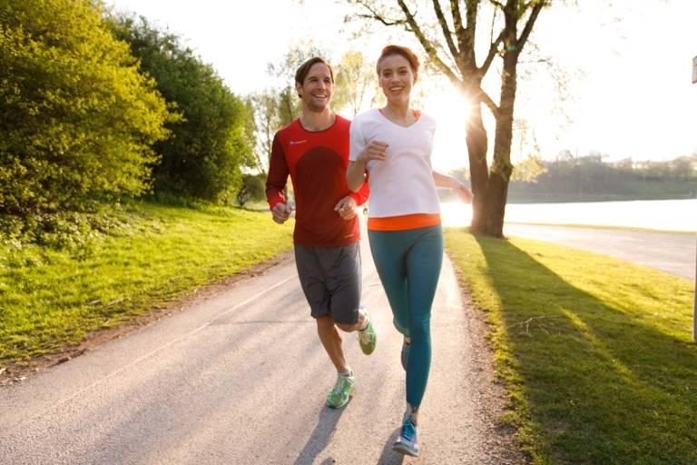 Ein Mann und eine Frau joggen in der Abendsonne durch den Olympiapark in München.