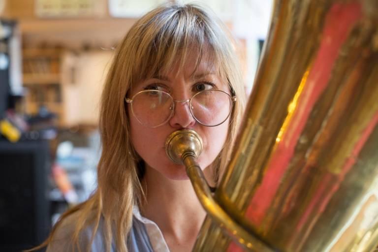 Journalistin spielt Tuba in einem Musikgeschäft in München.