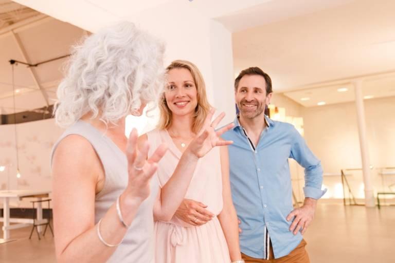 Eine Frau mit weißen Haaren erklärt einer Gruppe in der Ingo Maurer Lichtdesign Ausstellung in München die Werke.