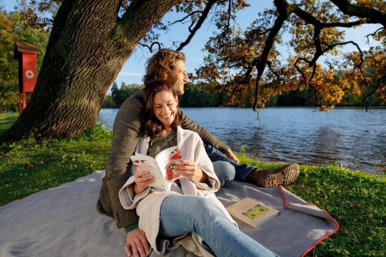 Ein Paar sitzt auf einer Picknickdecke im Nymphenburger Schlosspark in München an einem sonnigen Herbsttag.