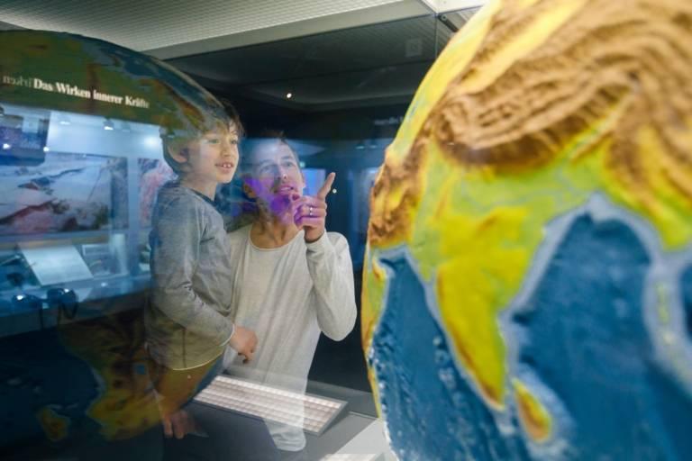 Ein Mann deutet mit dem Finger auf die Weltkugel im Schaukasten des Museums Mensch und Natur in München und zeigt diese seinem Jungen, den er auf dem Arm trägt.