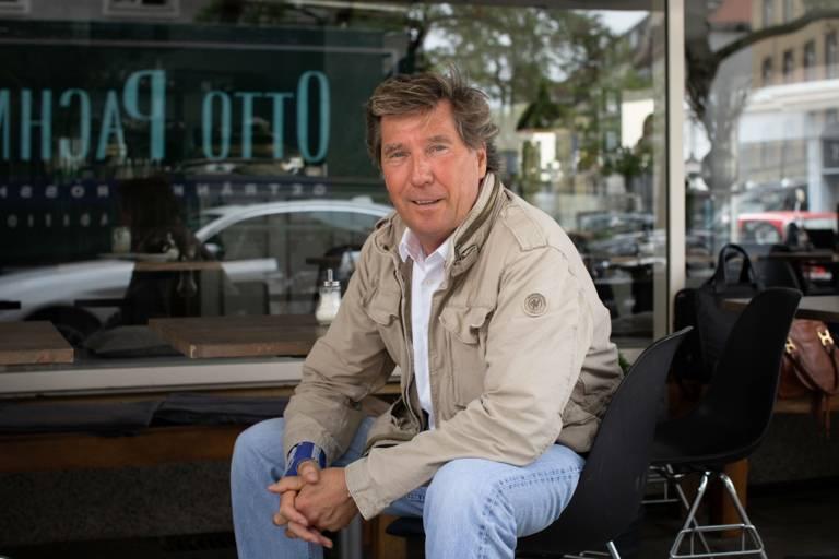Ein Mann sitzt vor einem Café und lächelt in die Kamera.