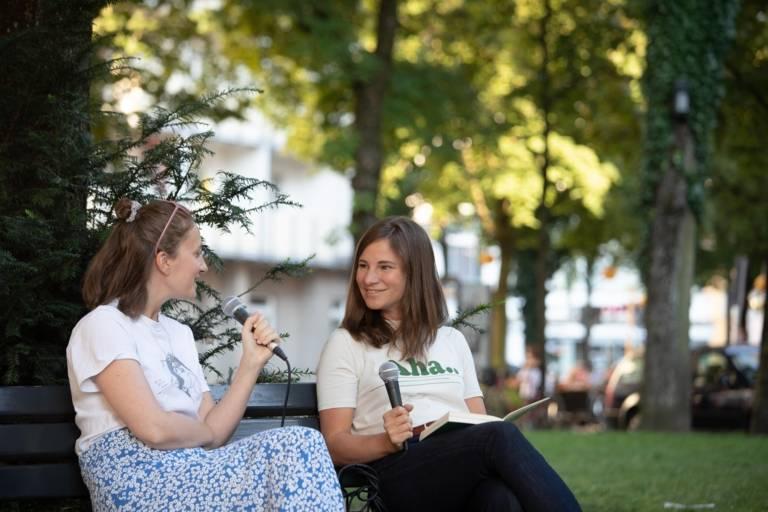 Zwei junge Frauen im Gespräch mit Mikrofonen in München.
