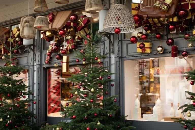 Geschmückte Weihnachtsbäume und Geschenke schmücken die Schaufenster