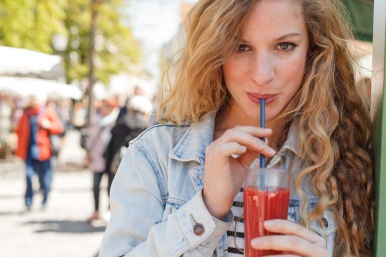 A woman is drinking a red smoothie at the Viktualienmarkt in Munich.