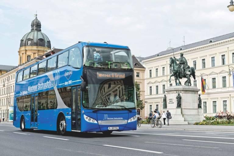 Ein blauer Doppeldecker-Stadtrundfahrtenbus der Firma GREY LINE fährt am König Ludwig I. Denkmal an der Ludwigstraße in München vorbei.