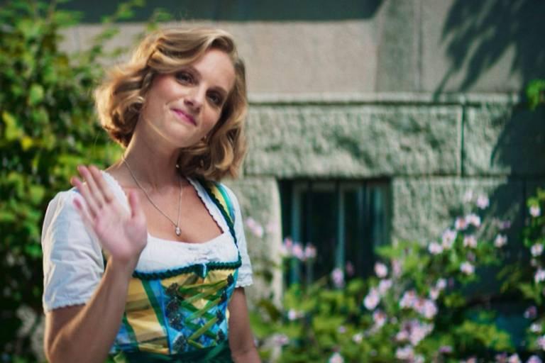 Eine Frau im Dirndl winkt in München