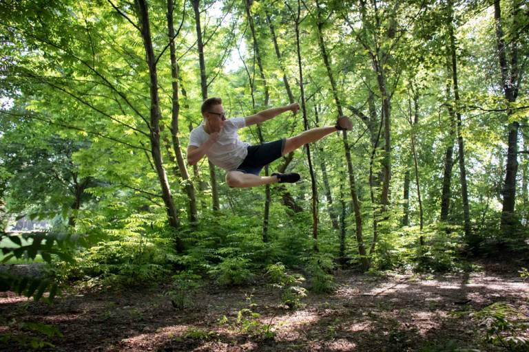 Junger Mann mit einer Aktion aus dem Taekwon-Do in einem Wald in München.