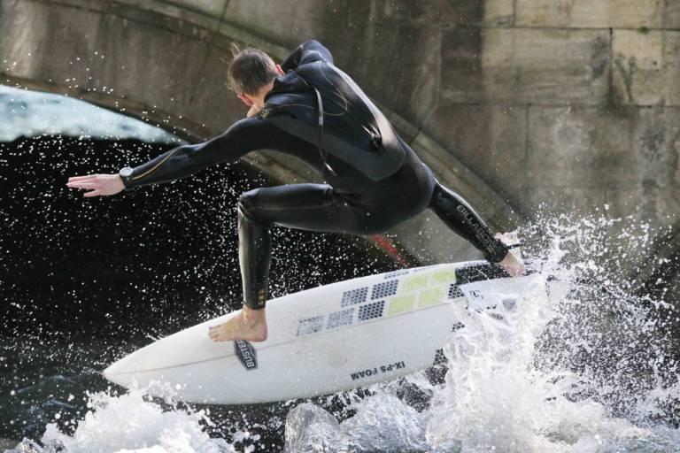An der Eisbachbrücke stehen Tag und Nacht Zuschauer*innen, die den Surfer*innen beim Wellenreiten zugucken.