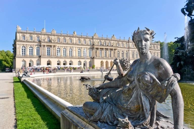 Blick auf den Brunnen und die Fassade des Schloss Herrenchiemsee. Auf dem Rand des Brunnens liegt eine steinerne Statue.
