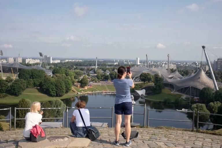 Drei Touristen auf der Aussichtsplattform des Olympiabergs mit Blick auf den Park und das Hinterland.