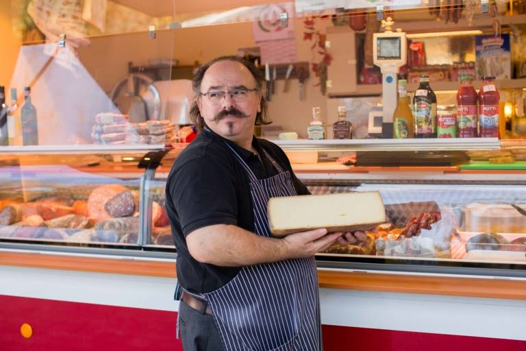 A salesman with a big piece of cheese in his hands at the weekly market at Hans-Mielich-Platz in Munich.