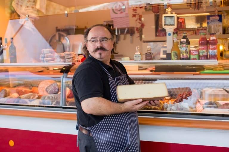 Ein Verkäufer mit einem großen Stück Käse auf dem Wochenmarkt am Hans-Mielich-Platz in München.