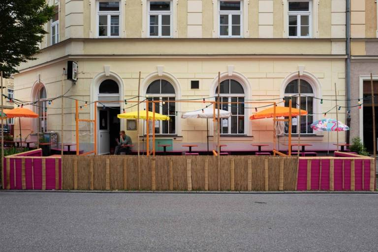 Ein bunter Schanigarten mit einem Geländer aus Bast und Bambus in München.