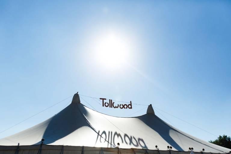 Ansicht eines großen Zeltdachs zwischen dem der Schriftzugs des Tollwood Festivals gespannt ist, darüber steht die strahlende Sonne am blauen Himmel.