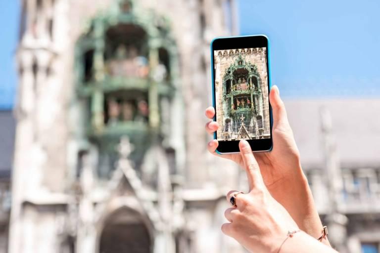 Eine Frau fotografiert mit ihrem Handy das Glockenspiel am Neuen Rathaus on München.