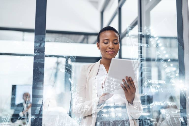 Eine Frau steht in einem modernen Konferenzraum und blickt auf ein weißes Tablet.