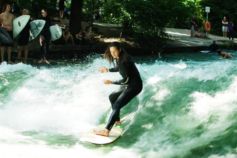 A female surfer surfing on the Eisbach in Munich