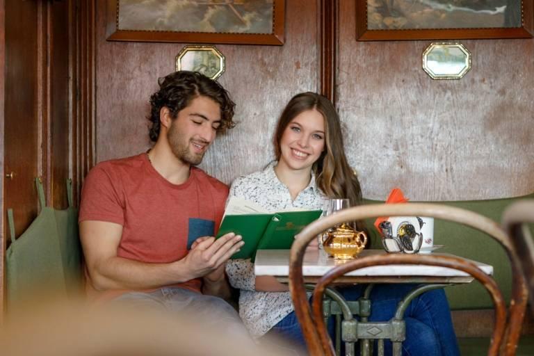 Ein junger Mann und eine junge Frau sitzen an einem Tisch im Valentin-Karlstadt-Musäum in München.