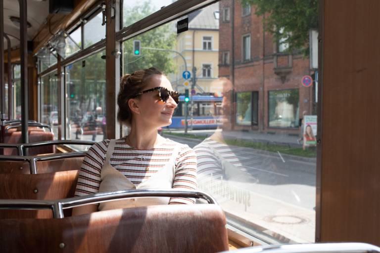 Junge Frau sitzt am Fenster in einer Tram in München.