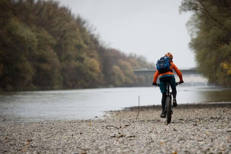 Eine Frau fährt im Herbst mit dem Mountainbike an der Isar entlang.