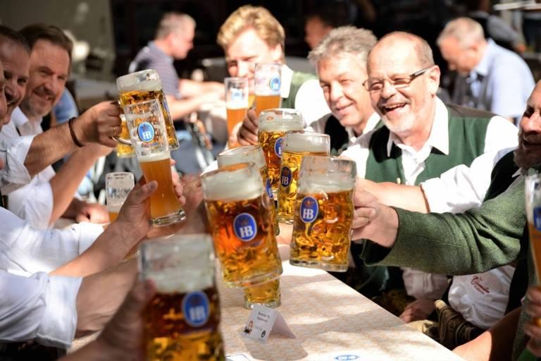 Ein Tisch mit Männern prostet sich im Biergarten des Hofbräuhauses in München zu.